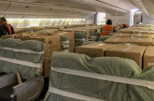 Packages secured in passager seats on an airplane.