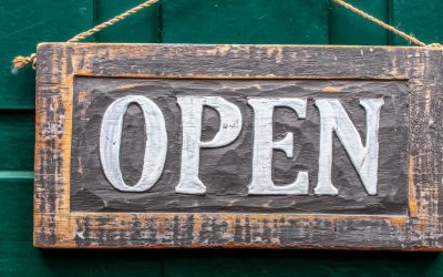 Wooden open sign with white lettering on a green door